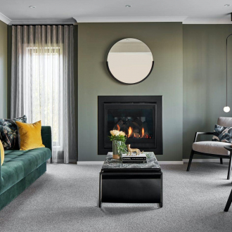 formal living room styling with dark green walls fireplace with round mirror above and velvet green sofa
