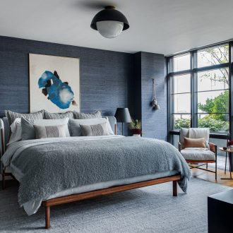 large bedroom rug with all furniture sitting on top dark blue cloth wallpaper
