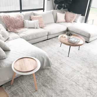 miss amara siraf white tribal pattern rug in living room with grey sofa and pink cushions- PP