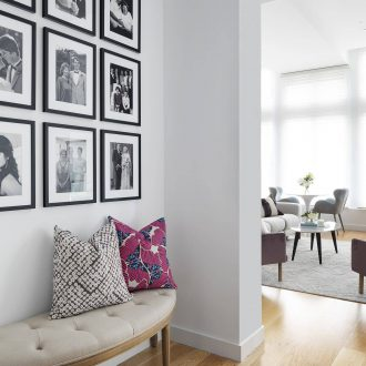 nine grid of black and white framed photos gallery wall above upholstered bench seat in entryway