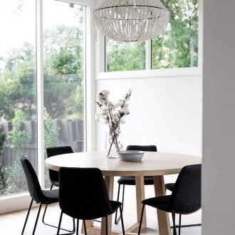 round oak dining table with black dining chairs