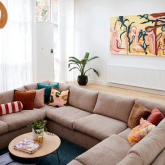 the block 2021 tanya and vito sunken living room with grey sectional sofa and coloured cushions
