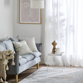white living room with grey sofa white sheer curtains face artwork